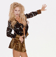 Photo of a blond glamour model. She's in a leopard print and vinyl mini skirt & jacket and a black lace bra.