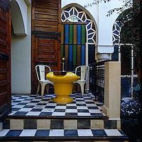 A yellow retro table and metal chairs stand on a raised terrace in the courtyard