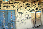 A bicycle and air pump, a fighter jet taking ground fire, an automobile and other graffiti decorate the wall of a shop in the village of Nakhonay, southwest of Kandahar, Afghanistan. Oct. 7, 2008. DREW BROWN/STARS AND STRIPES