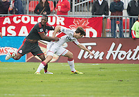 Toronto, Ontario - May 3, 2014: Toronto FC defender Doneil Henry #15 and New England Revolution forward Patrick Mullins #7 in action during a game between the New England Revolution and Toronto FC at BMO Field.<br /> The New England Revolution won 2-1.