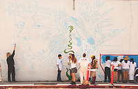 Artist Kristel Lerman, (left) with the help of kids from InsideOut Community Arts, paints a seascape mural on the side of ZJ's Boarding House on Thursday, July 26 2012. The mural is a collaborative project of Kristel Lerman,  Select NY, InsideOut Community Arts and ZJ's Boarding House.