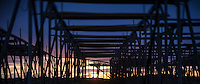 Silhouette shapes of empty cod drying racks at sunrise, Toppøy, near Reine, Moskenesøy, Lofoten Islands, Norway