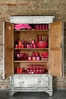 The interior of this antique cupboard has been colour-coordinated in vibrant shades of pink