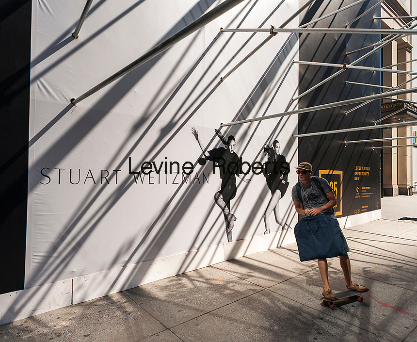 "A skateboarder swings by the construction shed for the new ""Coach House"" on Fifth Avenue in New York on Monday, August 29, 2016. Coach announced it will open a ritzy store on expensive Fifth Avenue in an effort the raise the luxury status of their brand. The space will be 23,400 square feet with the Weitzman store adjacent on the avenue where rents can run $4000 a square foot. The store is scheduled to open in Fall 2016. (© Richard B. Levine)"
