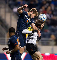Patrick Mullins (15) of Maryland goes up for a header with Zach Carroll (2) of Virginia during the NCAA Men's College Cup semifinals at PPL Park in Chester, PA.  Maryland defeated Virginia, 2-1.d