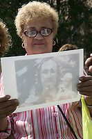 A woman examines a close-up photograph of a statue of Christ that rests in a small shrine on Jackson and Third streets in Hoboken, NJ, USA, to examine the eye that is said to have suddenly opened without human intervention a few days earlier in what locals believe is a sign from God, 31 July 2005. Photo Credit: David Brabyn