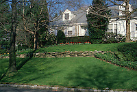 Tiered lawn with stone wall in spring and Cape Cod house, home landscaping with front entry curb appeal, tulips spring flowering bulbs
