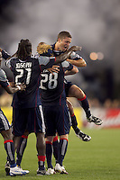 New England Revolution midfielder Chris Tierney (8) jumps in to celebrate New England Revolution defender Pat Phelan (28) goal with smoke from New England Endzone Militia in the background. The New England Revolution defeated DC United, 1-0, at Gillette Stadium on August 7, 2010.