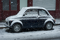 Small Fiat car covered with snow in a Paris street.