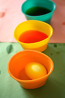 Photo of Easter Eggs being dyed in several cups of brightly colored dye.