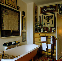 A collection of framed prints and antique documents cover the walls of this bathroom