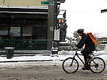 A bicycle messenger rides down 1st Avenue on a delivery after a snowstorm hit the Seattle area early Wednesday morning dumping at least 4 to six inches and will likely continue into the afternoon it a tough commute for drivers  in Seattle on January 18, 2012.  ©2012. Jim Bryant Photo. All Rights Reserved.