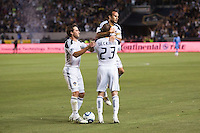 LA Galaxy's Landon Donovan (10) jumps in teammate David Beckham's (23) arms and begins the celebration as Todd Dunivant (2) moves in on the fun. The LA Galaxy and Red Bulls of New York played to a 1-1 tie at Home Depot Center stadium in Carson, California on  May 7, 2011....