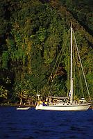 Woman aboard saling yacht 'Heron', at anchor off jungle shore of The Grottoes, Tahiti, French Polynesia