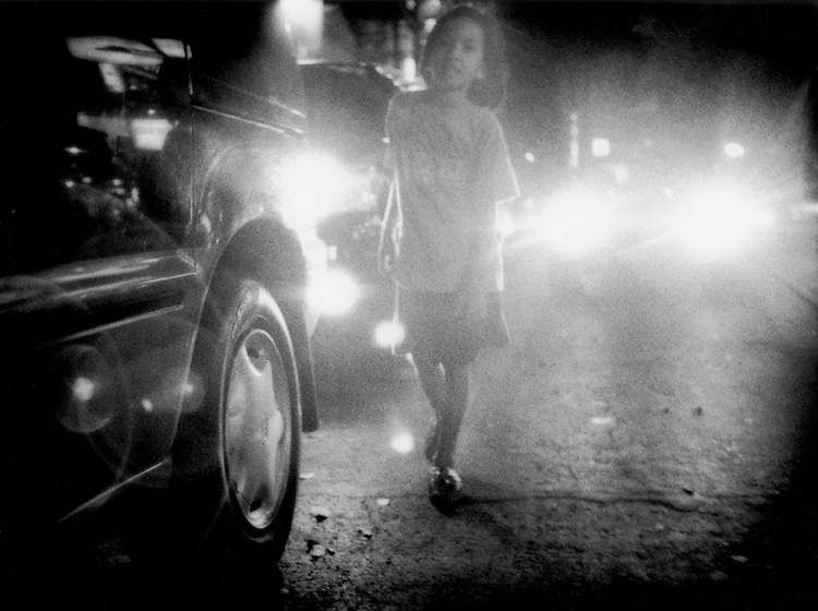 Street kid navigates Manila street after midnigh in the headlights of city traffic, Philippines.