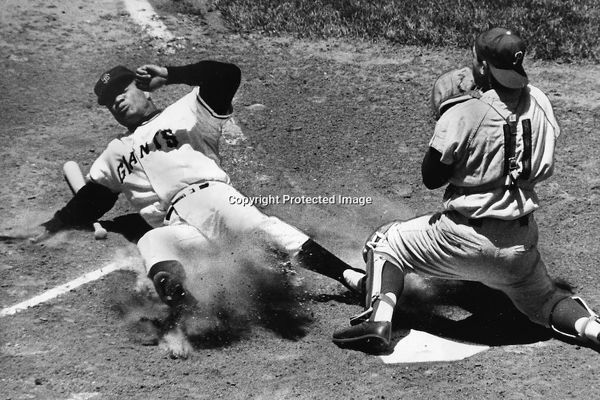Giants Felipe Alou slides safe into home, Philly catcher Clay Dalrymple takes the late throw.(1962 photo by Ron Riesterer)
