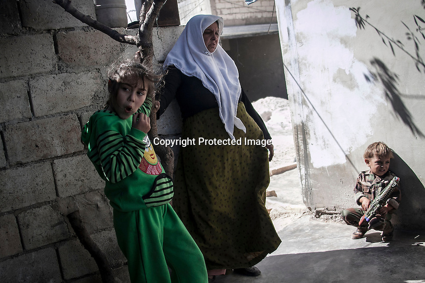 In this Thursday, Oct. 03, 2013 photo, the wife of MOHAMMED AHMED KALE (not pictured), stands with her grandaughter and grandson at the yard her family house in Kafr Lata, a ghost village in a top of a mountain subdued under heavy shelling and bormbardments due the fighting between opposition fighters and government forces in the Idlib province countryside of Syria. Mohammed's whole family, included his six sons with their families and four daughters, is one of two families, that refuse to leave the village despite the heavy bombardments as four of his sons fight at the frontline situated one km from home. (AP Photo)