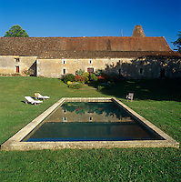 The swimming pool is set into the lawn behind the chateau