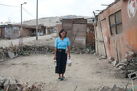 A woman outside her home on Tuesday, Apr. 14, 2009 in Ventanilla, Peru.