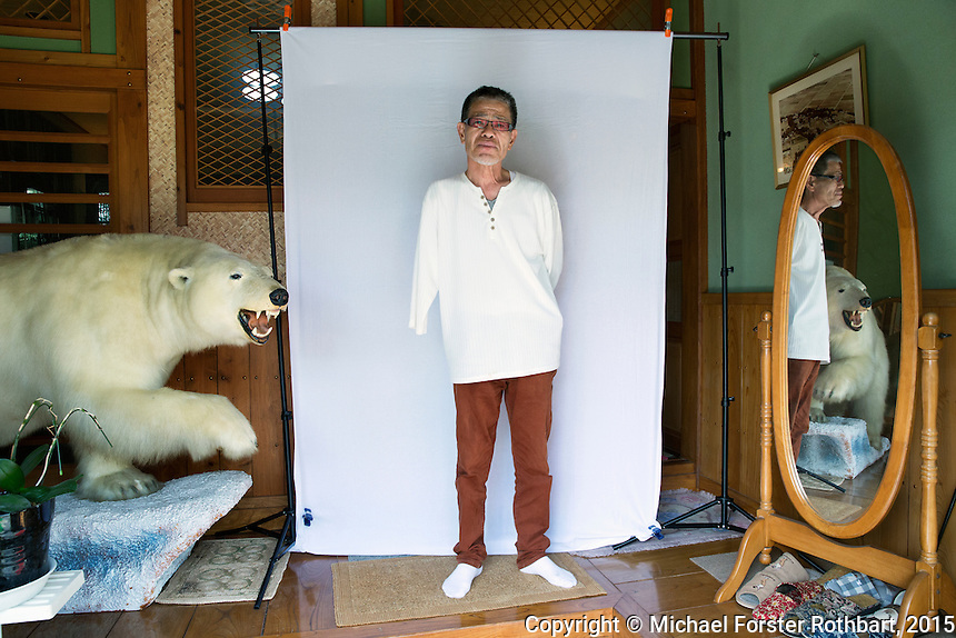 Fukushima evacuee Hisao Yanai stands for a portrait after returning home to his native town, Naraha, Japan, in the Fukushima Exclusion Zone, Sept. 30, 2015.  <br /> <br /> In March 2011, an earthquake and tsunami destroyed the Fukushima Daiichi nuclear power plant, 12 miles from Naraha. Some 488 thousand people evacuated; in 2015, nearly 25% remained displaced. Naraha is the first town to reopen since the disaster, following a massive decontamination campaign. Residents were allowed to return home full-time on Sept. 5, 2015. Only an estimated 100 residents have returned, out of a pre-disaster population of 7,400. <br /> <br /> When the tsunami hit, Hisao Yanai was head of the local Yakuza (Japanese mafia) in Naraha. He says the disaster changed him; he decided to leave the mafia and dedicate himself to helping people. He now owns a Japanese pub in Naraha, but kept many symbols of his former status, including a taxi-yellow Hummer and the stuffed polar bear in the foyer of his sprawling house. <br /> <br /> Just after this photo (part of a series for Mother Jones magazine) Yanai sat beside the bear, holding a whiteboard on his lap as he wrote with his one hand about his hope &mdash; &ldquo;Solidarity&rdquo; &mdash; and his worry for the future: &ldquo;how to accomplish the reconstruction of my hometown.&rdquo; <br /> <br /> &copy; Michael Forster Rothbart Photography<br /> www.mfrphoto.com &bull; 607-267-4893<br /> 34 Spruce St, Oneonta, NY 13820<br /> 86 Three Mile Pond Rd, Vassalboro, ME 04989<br /> info@mfrphoto.com<br /> Photo by: Michael Forster Rothbart<br /> Date:  9/30/2015<br /> File#:  Canon &mdash; Canon EOS 5D Mark III digital camera frame B17337