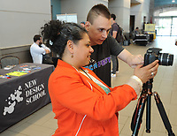 NWA Democrat-Gazette/ANDY SHUPE<br /> Sonia Gutierrez (left), founder and COO of New Design School in Fayetteville, photographs Brian Dodwell of Fayetteville Thursday, May 18, 2017, during Tech Fest  in the Fayetteville Town Center. New Design School currently operates out of a shared space with Startup Junkie on the square, but school officials hope to move to a permanent location on the first floor of the historic Walker-Stone House.