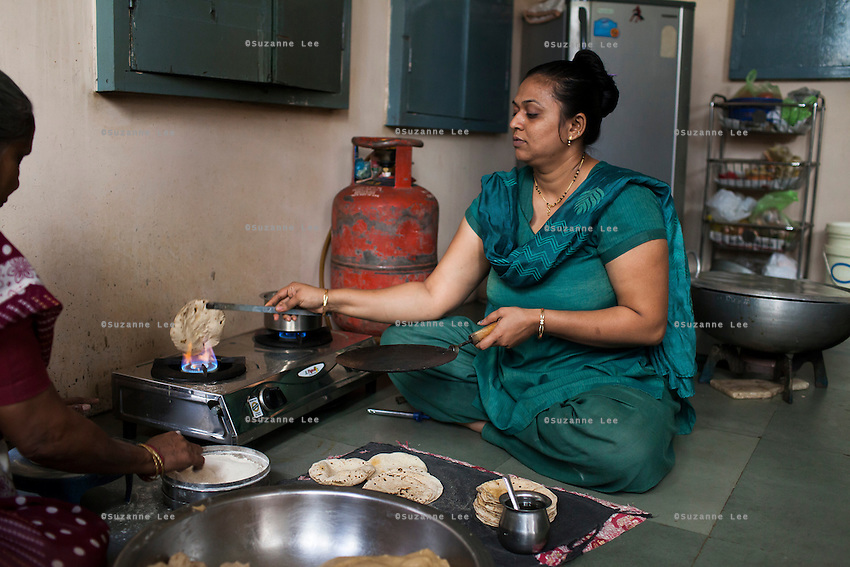 Archana, an ex-surrogate, cooks bread, as she continues to work with Dr. Nayana Patel, catering specially prepared tiffin meals to the surrogates and Akanksha IVF and Surrogacy clinic staff, which she prepares in her house with her family in Anand, Gujarat, India on 11th December 2012. Photo by Suzanne Lee / Marie-Claire France