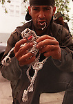 A man makes small figures out of twist-ties and sells them on Haight Street in San Francisco, California.