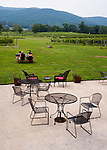 Philip Carter Winery's tasting facility is surrounded by lawns and vineyards, with outdoor seating on the patio and at picnic tables out on the grass.