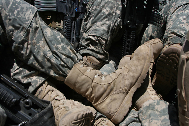 With temperatures hovering around 115 degrees, tired soldiers crowd the back of a five-ton truck under a scorching afternoon sun as they wait for transport back to their bases near Mahmudiyah, Iraq. July 11, 2007. DREW BROWN/STARS AND STRIPES
