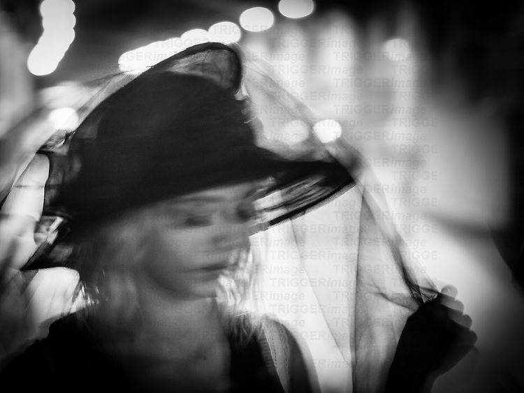 Blurred subject movement shot of blonde girl in a hat