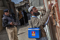A Pakistani health officer writes information about vaccination for poliomyelitis at a gate under tight security, during door-to-door 'Anti-polio campaign' in Karachi, Pakistan on Jan. 19, 2015