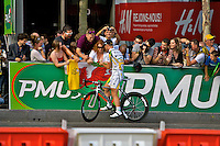 Mark Cavendish stops to sign his autograph for fans who line the streets of Paris during the 2010 Tour de France