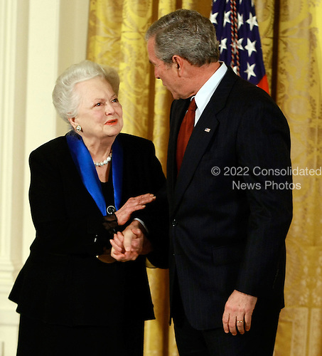 Washington, DC - November 17, 2008 -- United States President George W. Bush congratulates actress Olivia de Havilland after presenting her with the 2008 National Medals of Arts award during an event in the East Room at the White House on Monday, November 17, 2008 in Washington, DC. During the event president Bush presented recipients with awards for the National Medals of Arts and the National Humanities Medal..Credit: Mark Wilson - Pool via CNP