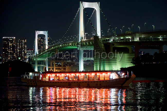 "The lights of a ""yakata-bune"" pleasure boat are reflected in the calm waters of Tokyo Bay as it passes by Rainbow Bridge in Tokyo, Japan on 31 August  2010. .Photographer: Robert Gilhooly"