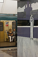"""Moscow, Russia, 20/06/2010..Passengers and a mural depicting Svidrigailov's suicide in Crime & Punishment at the just-opened Dostoevsky metro station, the newest in Moscow's underground metro system. The station's opening was delayed by several weeks after psychiatrists claimed the gloomy and violent images in murals depicting scenes from Dostoevsky's novels would make the station a """"mecca for suicides""""."""