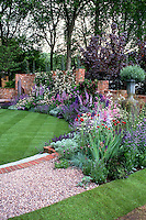Glorious gorgeous flower perennial garden with lawn, steps, Delphinium, Knautia, Salvia, climbing vine on brick wall, pot container. Design by Xz Tollemache and Jon Kellett, 2003 Chelsea Flower Show Silver Gild medal winner