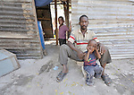 A man and his children sit outside the temporary home he built in a camp for homeless families in the Belair section of Port-au-Prince, Haiti. The country was wracked by a devastating earthquake on January 12, 2010.