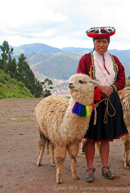 Peru. Woman in traditional dress stands with llama in the Andes