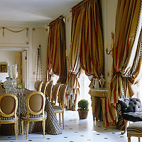 Dramatic, heavily layered curtains dress the windows of this dining room and echo the striped fabric used to upholster the suite of dining chairs