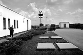 Mzizovice, Czech Republic.July 1997.Behind a highway gas station a McDonald's sign rises above the landscape. This American fast food Restaurant chain has become a symbol of the transition in much of Eastern Europe..