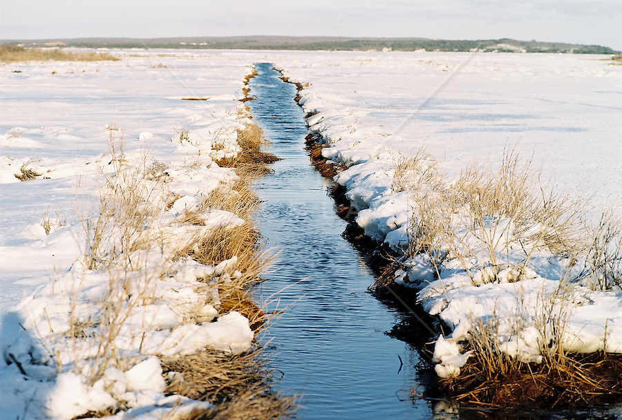 Stream amid snow-covered landscape