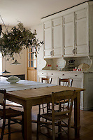 In the kitchen a massive antique dresser takes up an entire wall next to the old pine table and rush-bottom chairs