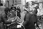 Hot roasted chestnuts and toffee apple market trader. Roman Road market east London England 1975