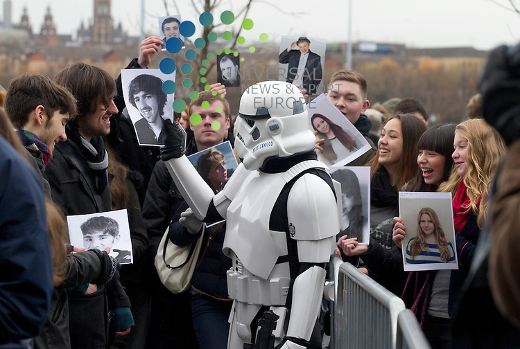 A stormtrooper looks at head shots as open auditions for the next Star Wars film will be held in Glasgow. Lucasfilm/Disney will be looking for two hopefuls for lead roles at Glasgow Science over this weekend. Previous auditions at Wasp Studios in Glasgow were postponed earlier this month to allow a larger venue to be booked amid huge expected interest.<br /> Star Wars: Episode VII is due to begin shooting at Pinewood Studios in spring 2014, for an expected 2015 release.<br /> Disney bought Lucasfilm, the production company behind the Star Wars series, in October 2012.<br /> Picture: Maurice McDonald/Universal News And Sport (Europe) 30 November  2013
