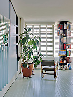 Carousel bookcases are a feature of the open plan living room which has louvered shutters on the windows to filter the natural light