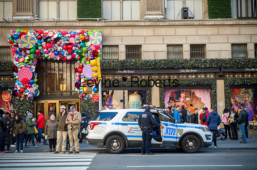 NYPD officers in front of the holiday decorations on Saks Fifth Avenue in Midtown Manhattan in New York on Sunday, November 27, 2016. The National Retail Federation reported that 43.8% of consumers shopped online during the four-day weekend.  (© Richard B. Levine)