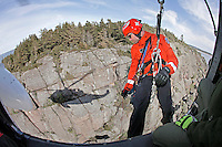 Rescue paramedic Lars Markengbakken standing in the side door of the helicopter, about to be lowered with the rescue hoist.<br />