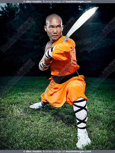 Portrait of a Shaolin warrior monk in a gong bu stance with a broad sword practicing Kung Fu outdoors