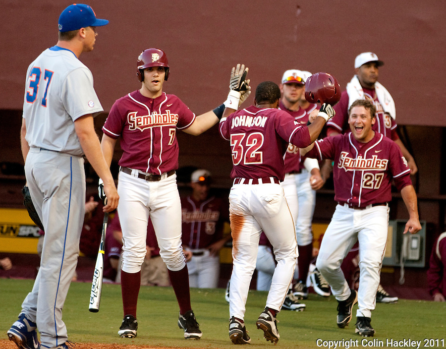 TALLAHASSEE, FL 4/12/11-FSU-UF BASE11 CH-Florida State's Sherman Johnson, center, scores the first of two runs off wild pitches against Florida during seventh inning action Tuesday at Dick Howser Stadium in Tallahassee. The Seminoles beat the Gators 3-1. COLIN HACKLEY PHOTO