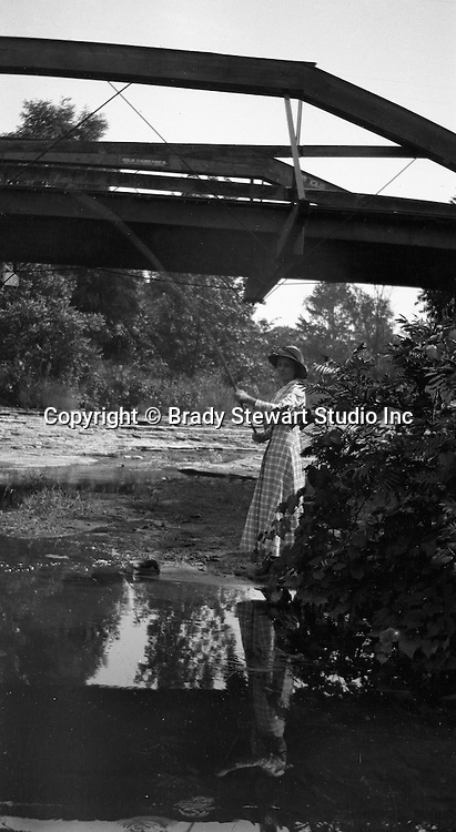 Erie PA: Woman fishing upstream from her husband and son on a stream near Lake Erie - 1915